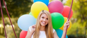 smiling girl on swing with balloons